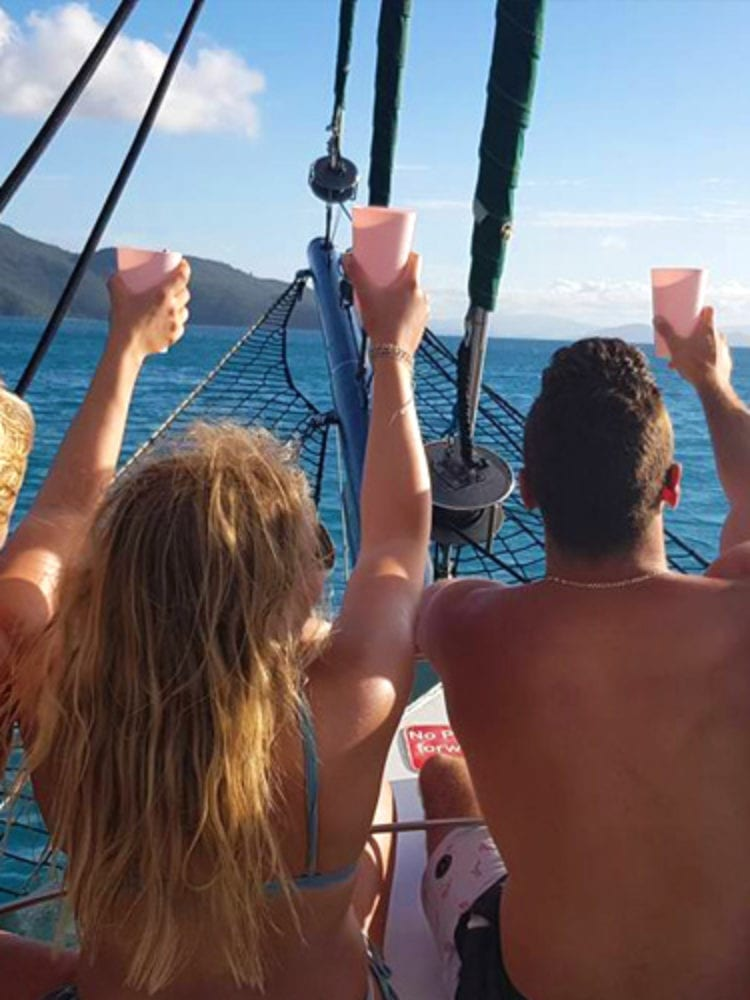Whitsunday Islands sailing holiday - guests on the bow of Atlantic Clipper sailing boat